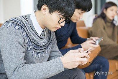 几个人坐在一起玩手机,www.yiyingbk.com